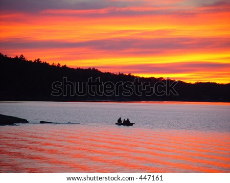Silhouette of a family in a kayak at sunset - stock photo