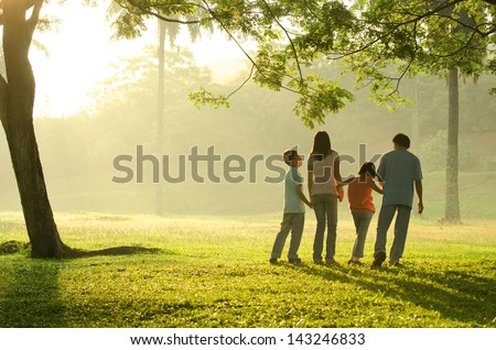 silhouette of a family walking in the park during a beautiful sunrise, backlight - stock photo