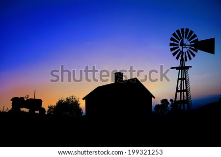 Silhouette of a farm tractor, house and windmill. - stock photo