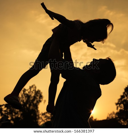 silhouette of a father and daughter who play outdoors at sunset background - stock photo