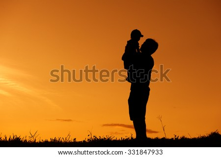 silhouette of a father and son playing outdoors at sunset with copy space - stock photo