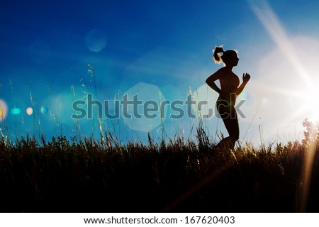 Silhouette of a female jogger with sun flare  - stock photo