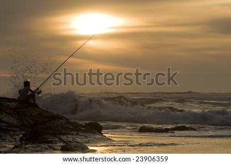 silhouette of a fisherman at a beach in Portugal - stock photo