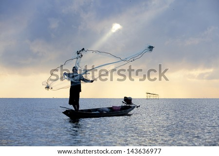 Silhouette of a fisherman throwing his net with beautiful sky. - stock photo