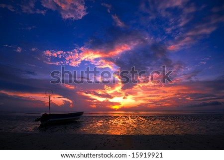 SIlhouette of a fishing boat on one of the beaches in Pahang, Malaysia. - stock photo