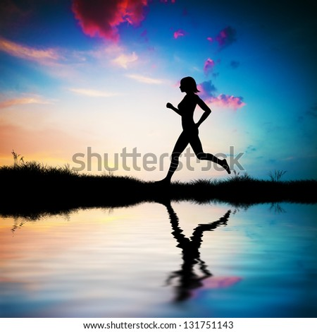 Silhouette of a fit woman running at sunset. Water reflection - stock photo