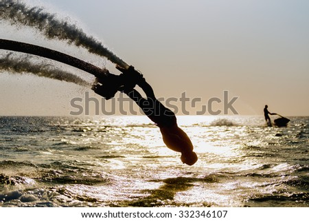 Silhouette of a fly board rider at sea - stock photo