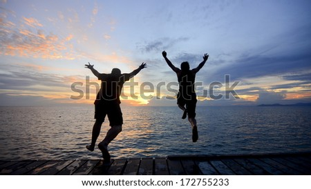 silhouette of a friend jumping into the sea during golden sunset. - stock photo
