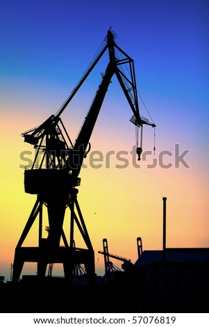 Silhouette of a giant crane at the harbor at sunrise - stock photo