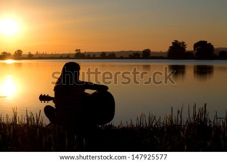 silhouette of a girl at sunset playing the guitar by the river - stock photo