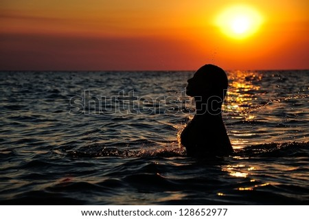 silhouette of a girl in ocean on sunset - stock photo
