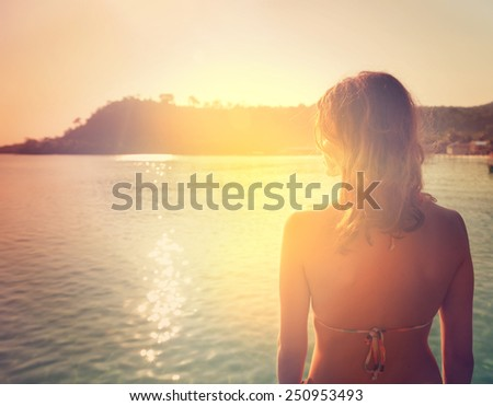 silhouette of a girl on a background of a sunset over the sea - stock photo
