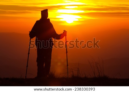 Silhouette of a girl on a mountain top on fiery orange background with trekking sticks - stock photo