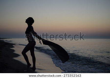 silhouette of a girl on the beach - stock photo