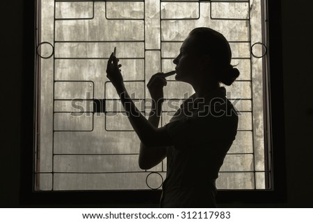 Silhouette of a girl paints her lips in front of a window behind which the wall - stock photo