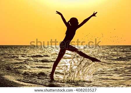 Silhouette of a girl running in the sea  in a spray of water at orange sunset - stock photo