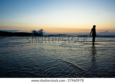 Silhouette of a girl standing on a Beach - stock photo