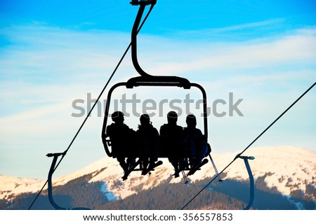 Silhouette of a group of people on a ski lift at ski resort. - stock photo