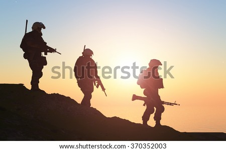 Silhouette of a group of soldiers at sundown. - stock photo