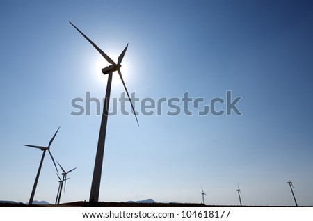 silhouette of a group of windmills for renewable electric energy production - stock photo