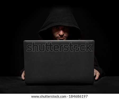 Silhouette of a hacker looking in camera with laptop on table - stock photo