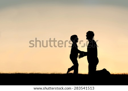 Silhouette of a happy little child greeting his father to hug him outside on a summer day, silhouetted against the sunset in the sky. - stock photo