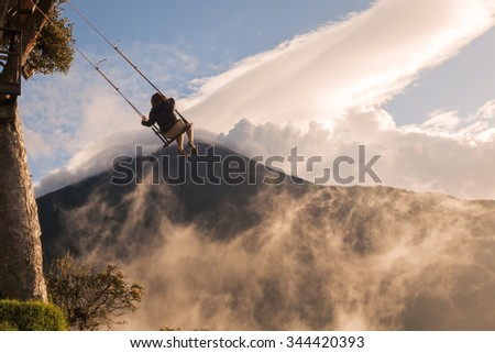 Silhouette Of A Happy Tourist Girl Swinging On A Swing Above The Andes Mountains, Tungurahua Volcano In Background   - stock photo
