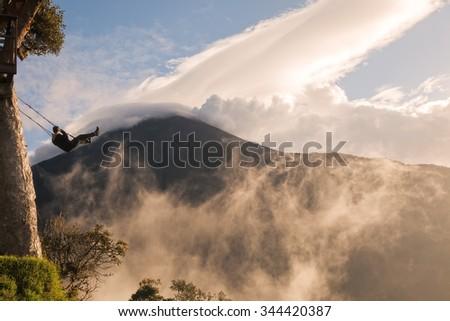 Silhouette Of A Happy Young Teenager Swinging On A Swing Above The Andes Mountains, Tungurahua Volcano In The Background  - stock photo