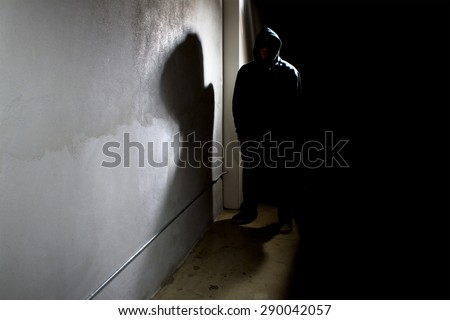 Silhouette of a hooded criminal stalking in the shadows of a dark street alley.  The man is a criminal waiting to ambush victims. The wall provides copyspace. - stock photo