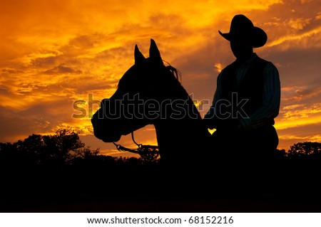 Silhouette of a horse and a rider against dramatic evening storm clouds - stock photo