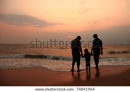 Silhouette of a kid and two adults playing in a beach during sunset - stock photo