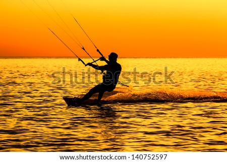 Silhouette of a kitesurfer sailing in the sea at sunset  - stock photo