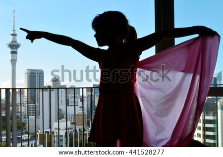 Silhouette of a little girl (age 6) role play to be a super girl superhero. Child on the background of city skyline. Girl power concept - stock photo