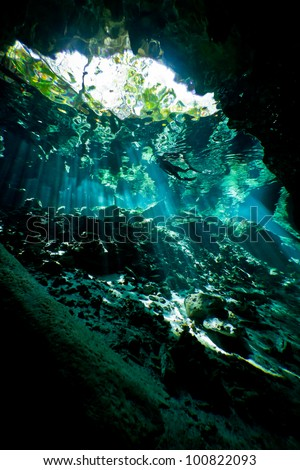 Silhouette of a lone female snorkeler from inside an underwater cave system in mexico. - stock photo