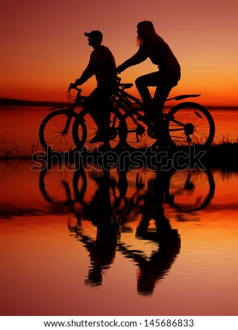 silhouette of a loving couple at the yellow or orange sunset sky background with reflection on water Copy space for inscription - stock photo