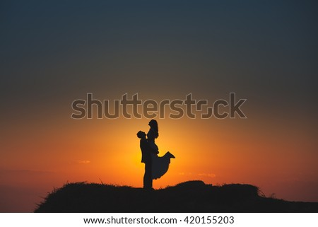 Silhouette of a loving couple on the background of the setting sun, mountains, islands and sea. Santorini. Greece. Just married. Walk. Walk at sunset. Walk through the mountains at sunset. - stock photo