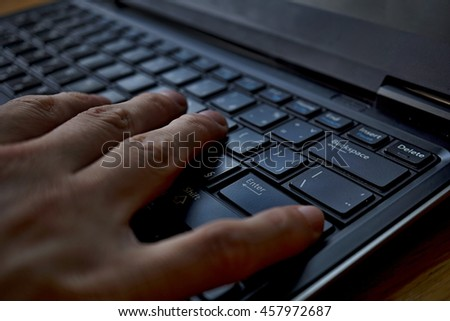 Silhouette of a male finger pressing black key with a caption Enter on the laptop keyboard  - stock photo
