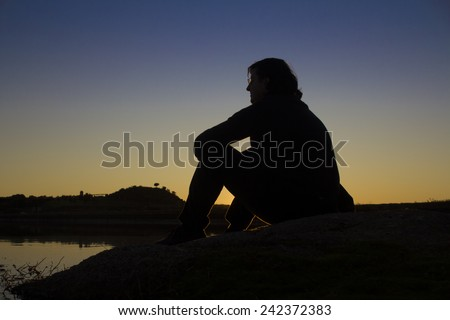 Silhouette of a man at dawn or sunset with an orange glow over the mountains sitting on a rock overlooking a tranquil lake enjoying the serenity and beauty of his surroundings - stock photo
