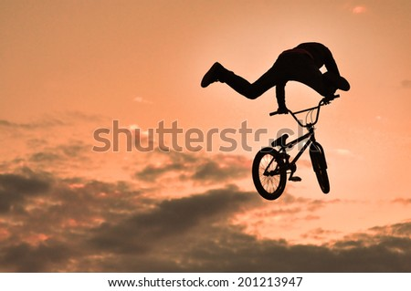 Silhouette of a man doing a jump with a bmx bike  - stock photo