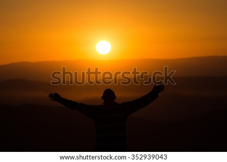 Silhouette of a man greets the sunrise in the desert - stock photo