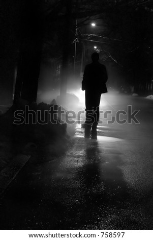Silhouette of a man in front of a bright light outside on a cold winter night. - stock photo