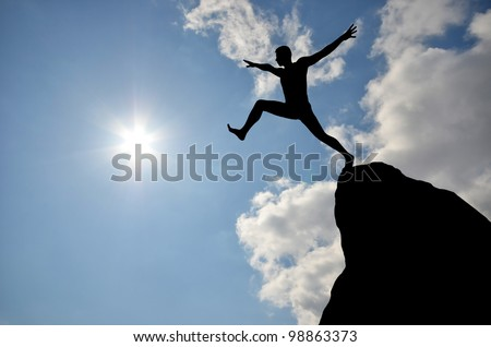 silhouette of a man jumping off a cliff in the direction of the bright sun - stock photo