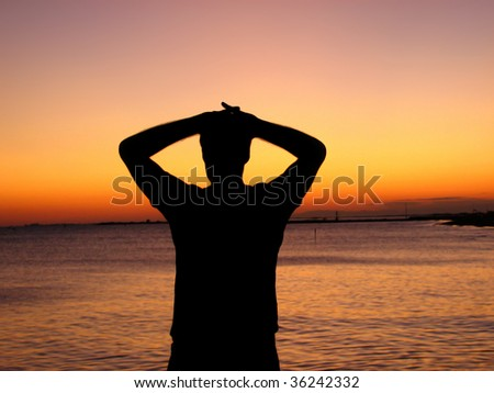 Silhouette of a man looking at the sunset over the ocean - stock photo
