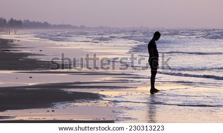 Silhouette of a man on a beach - stock photo