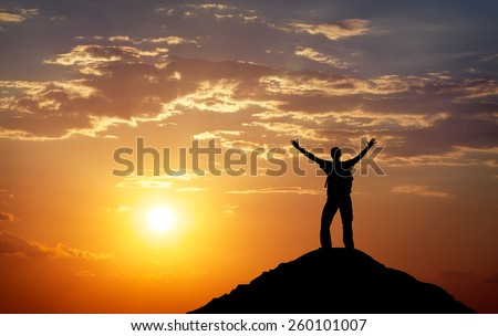 Silhouette of a man on a mountain top. Person silhouette on the rock. Sport and active life concept  - stock photo