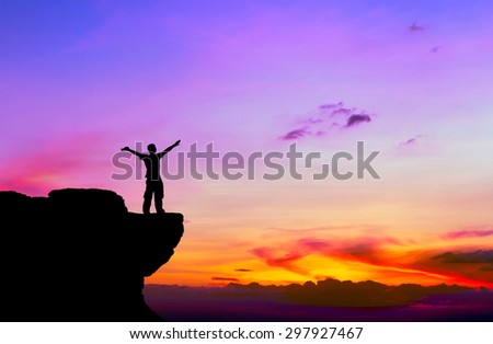 Silhouette of a man on the rock at sunset - stock photo