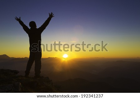 Silhouette of a man on top of a mountain, raising his hands in joy. - stock photo