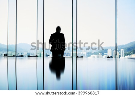 Silhouette of a man owner of trading company in real estate is looking into window and thinking about future meeting with client. Intelligent male professional banker is standing in conference room - stock photo