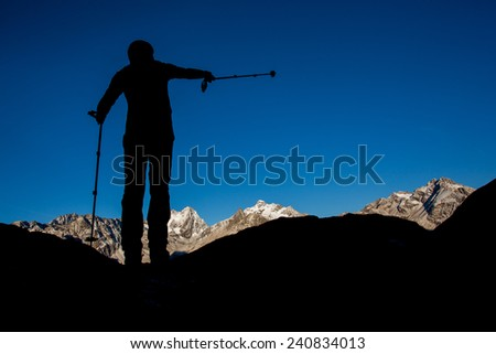 Silhouette of a man pointing with trekking pole towards mountain summit - stock photo