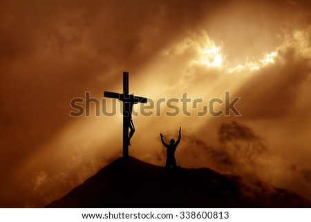 Silhouette of a man praying before a cross at sunset concept of religion - stock photo